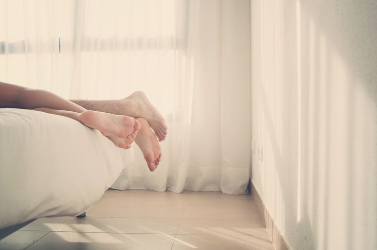 man and woman's feet hanging off the edge of a bed