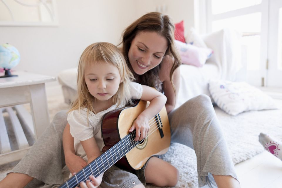 A picture of a mom and daughter playing guitar