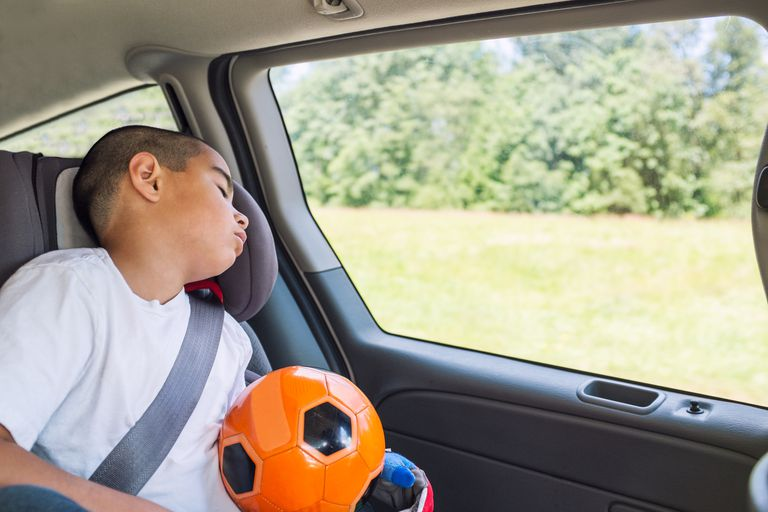 A child asleep in the car on the way to soccer practice.
