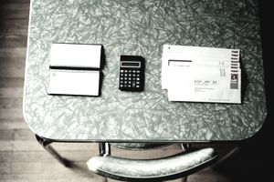 A table with bills, a checkbook, and a calculator