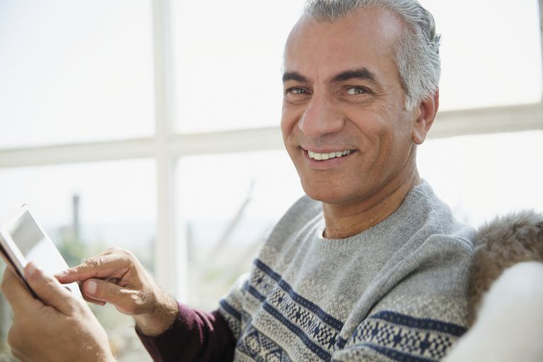 Portrait smiling senior man using digital tablet