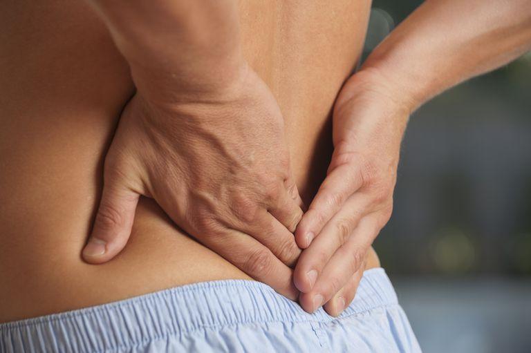 Man rubbing his lower back.