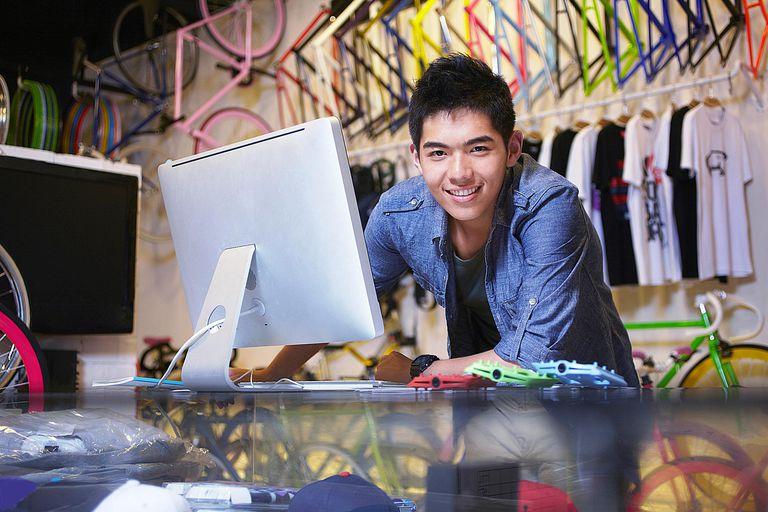 Young man in bike shop using computer