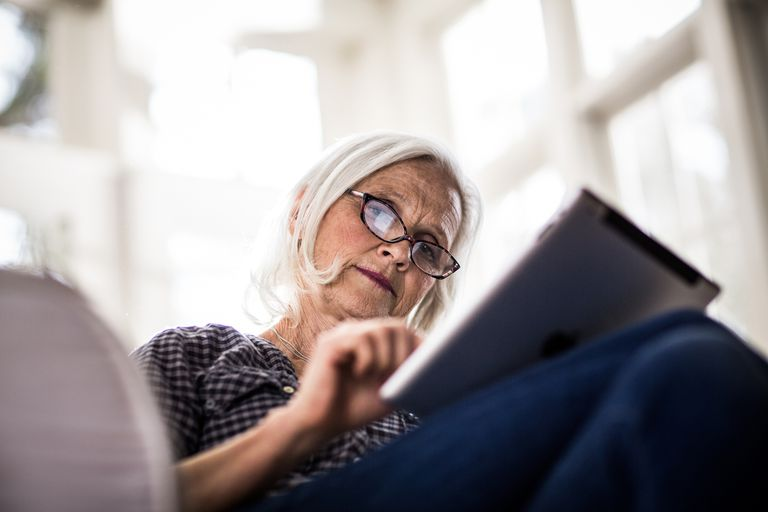 Older woman using social media on a tablet.