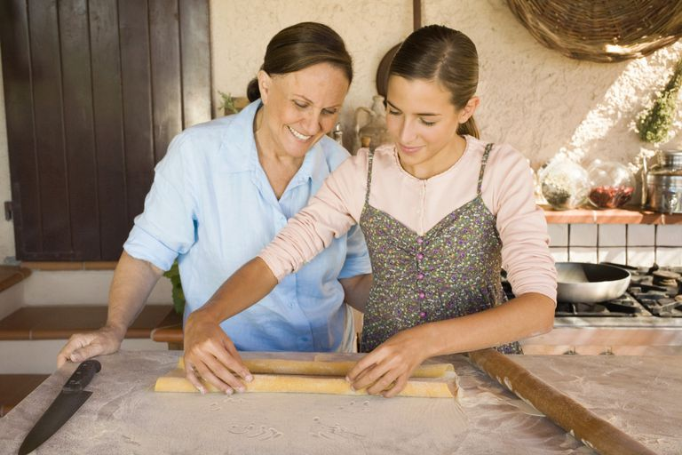 Grandmother with granddaughter rolling fresh pasta dough