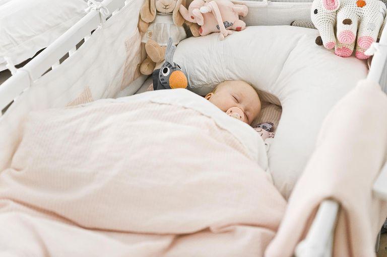 Danish baby girl sleeping in crib with bumper
