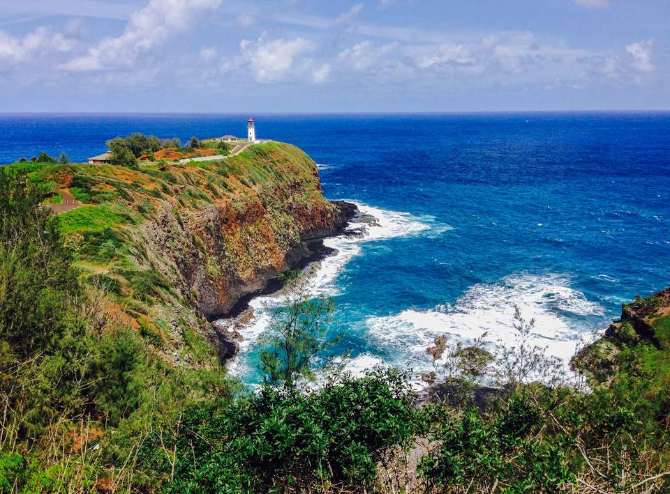Blue ocean water and lush vegetation surround Kilauea Lighthouse, located on the North Shore of Kaua'i, Hawaii.