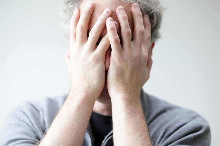 Distressed man with hands over his face