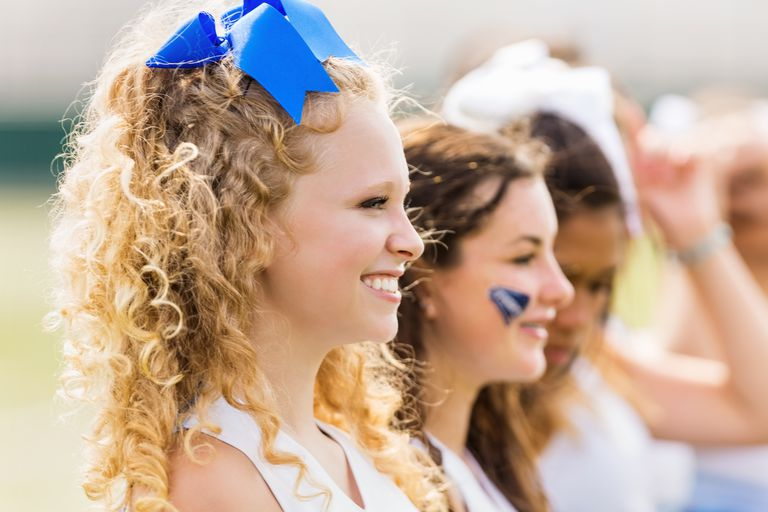 Competitive cheerleading squad cheering at football game
