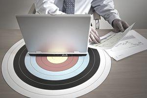 Businessman at desk with laptop on target