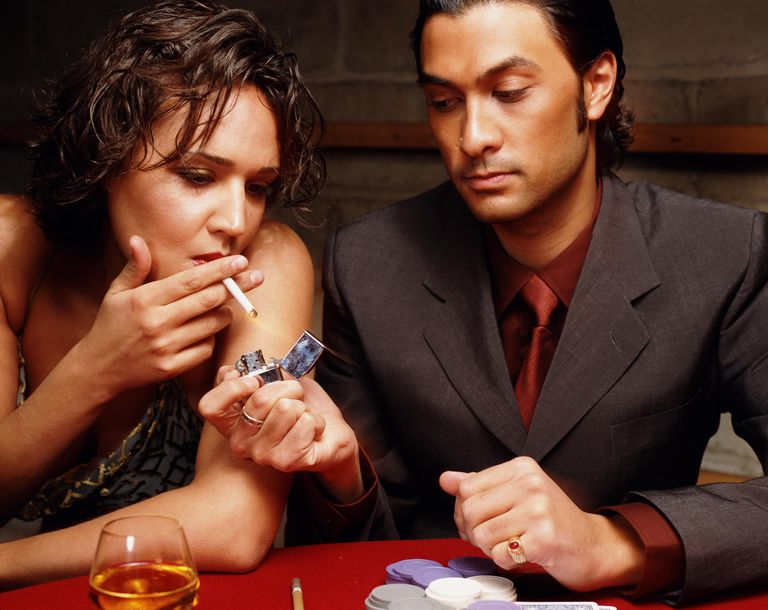 Man offering light to woman at gambling table