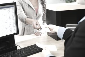 Financial transaction at customer service desk, handing a money order over