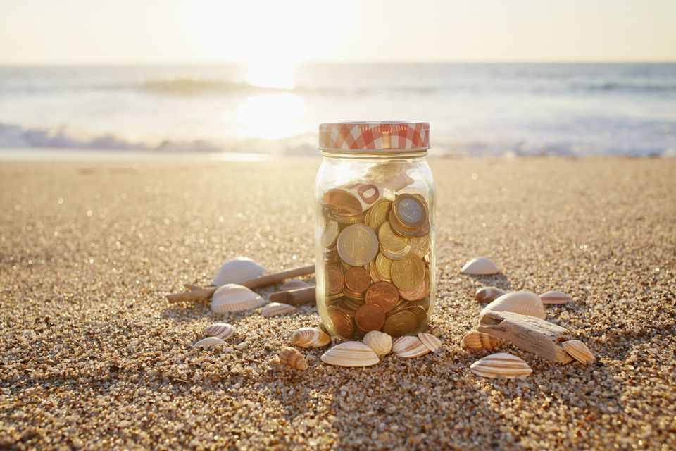 Euro bank note and coins in jar at the beach during sunset