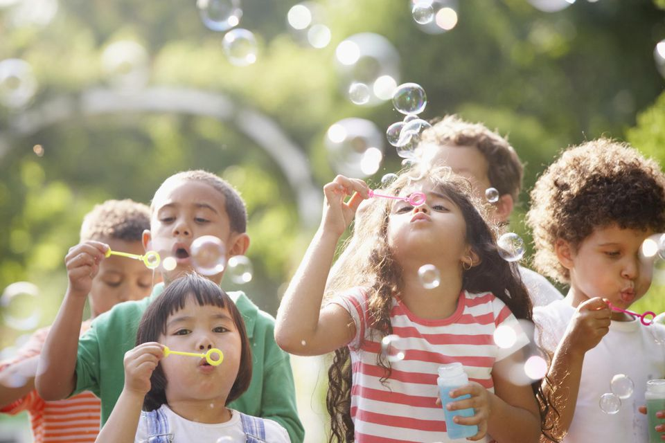 Children outdoors blowing bubbles.