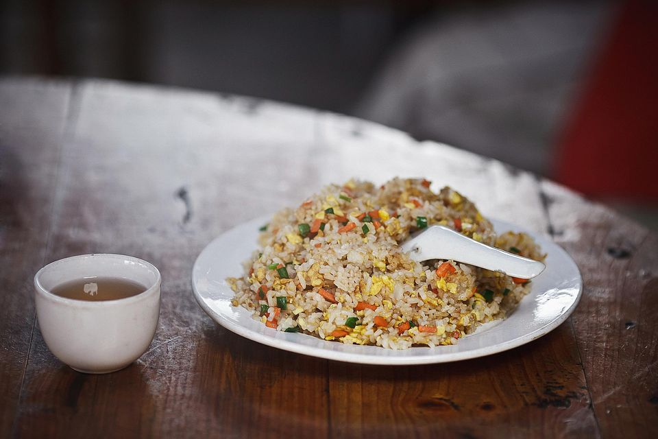 A plate of chicken fried rice with tea
