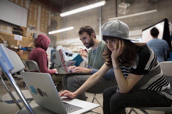 Focused female hacker wearing baseball cap working hackathon at laptop in workshop