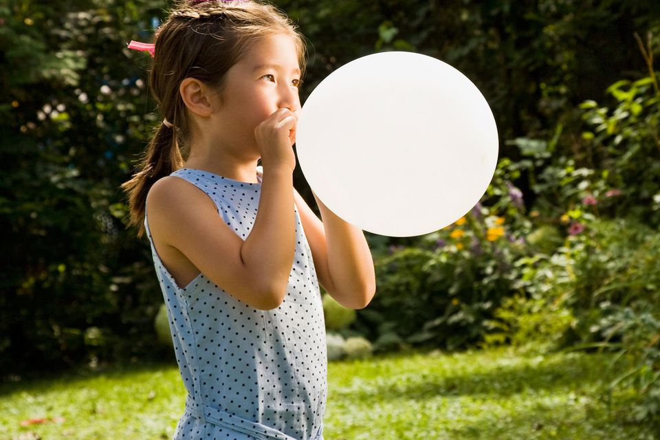 Young girl blowing up a balloon