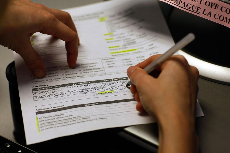 Marie Annoval, who was laid off from her job last month, fills her work history on an application for unemployment benefits at the employment help center Workforce One December 5, 2008 in Miami, Florida.