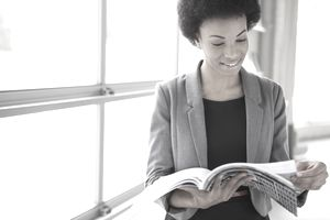 Woman reading magazine in office