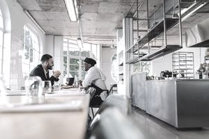 Business manager and chef talking in a restaurant