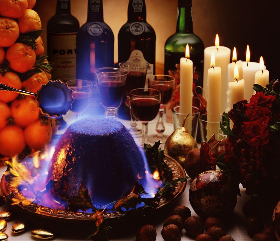 Flaming christmas pudding on set table, close-up