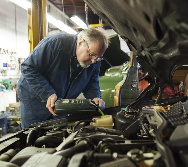 Mechanic pours antifreeze into engine