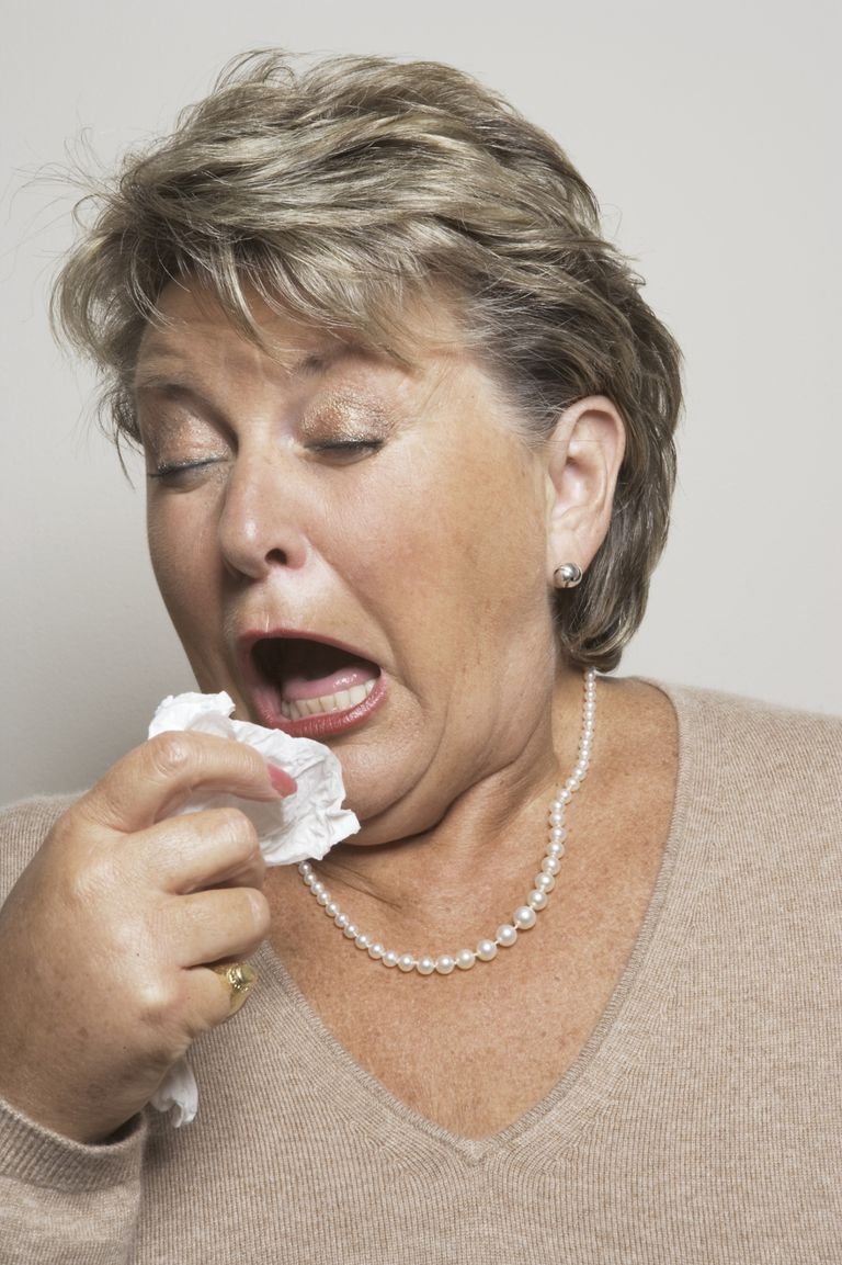 Mature woman holding handkerchief about to sneeze,