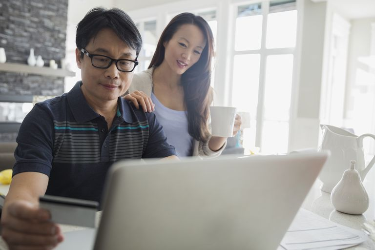 Father and daughter with credit card at laptop
