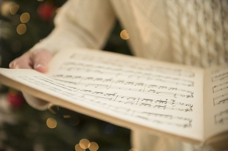 woman holding sheet music at christmas