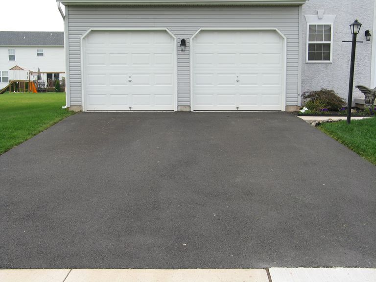 A double garage with white doors at the end of a driveway