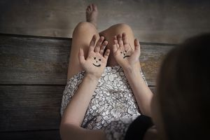 Picture of a Woman with Happy and Sad Faces on Her Hands, Choosing Her Attitude