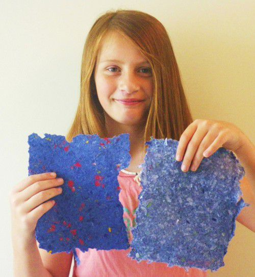 Sam holds up handmade paper she made from recycled old paper.