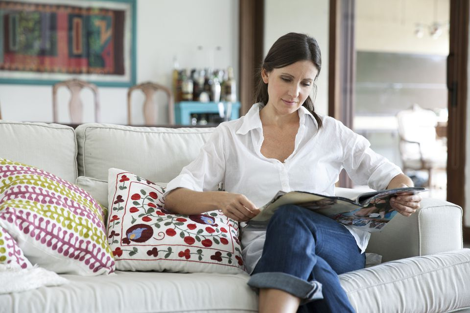 Woman sitting on sofa reading magazine