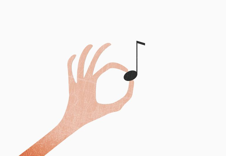 Hand holding musical note against white background