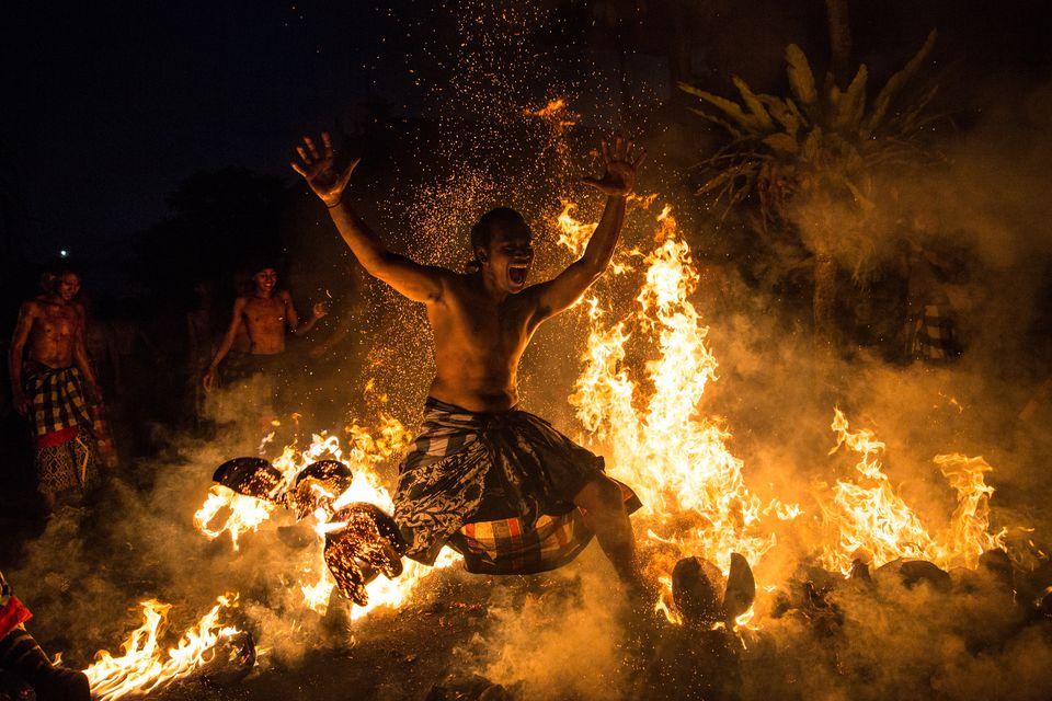 Balinese man dancing in fire before Nyepi