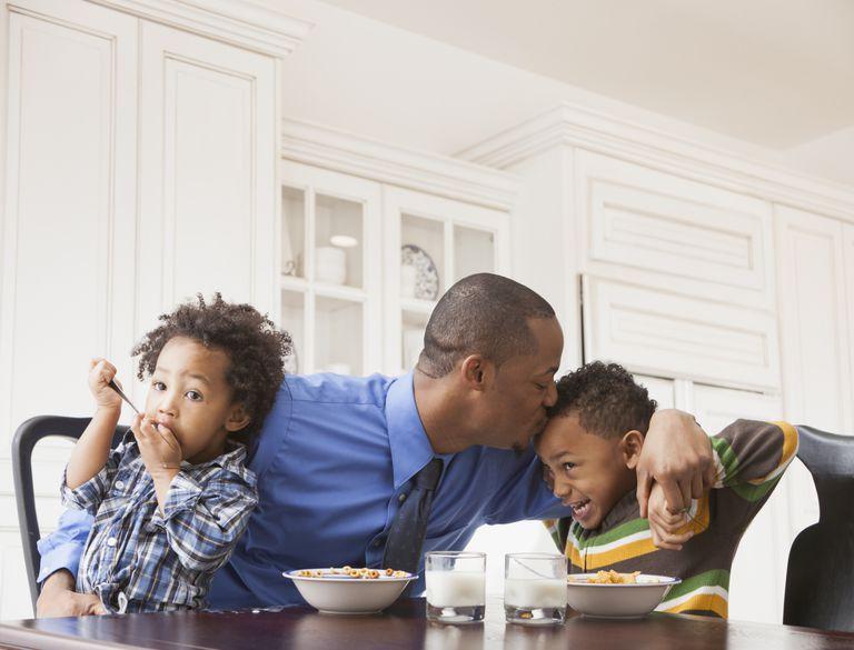 Father kissing sons at breakfast table.