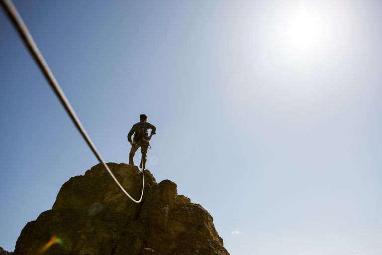 Man climbing a cliff tied by a rope