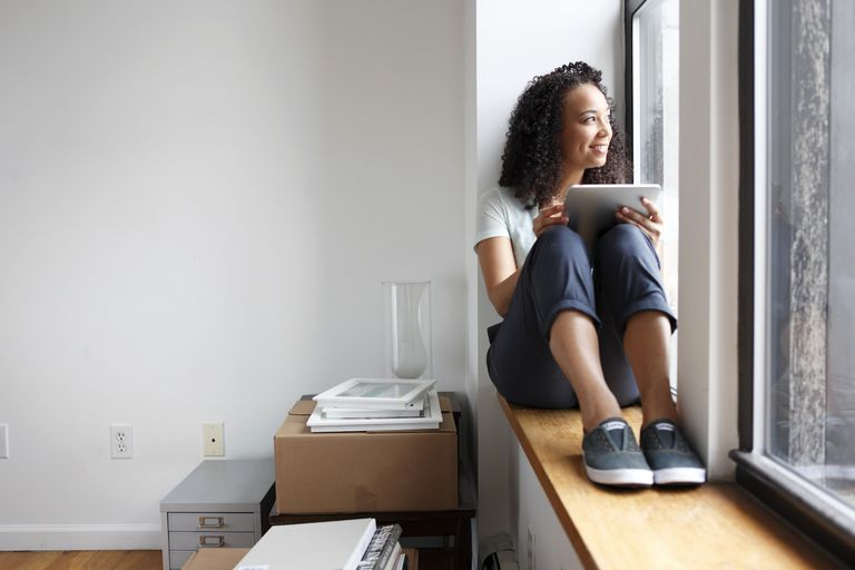 Woman near window with digital tablet in new home
