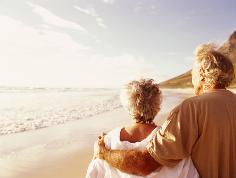 Senior couple embracing on beach, rear view