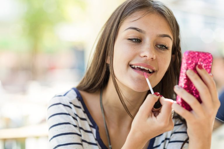 Teen girl fixing her make up