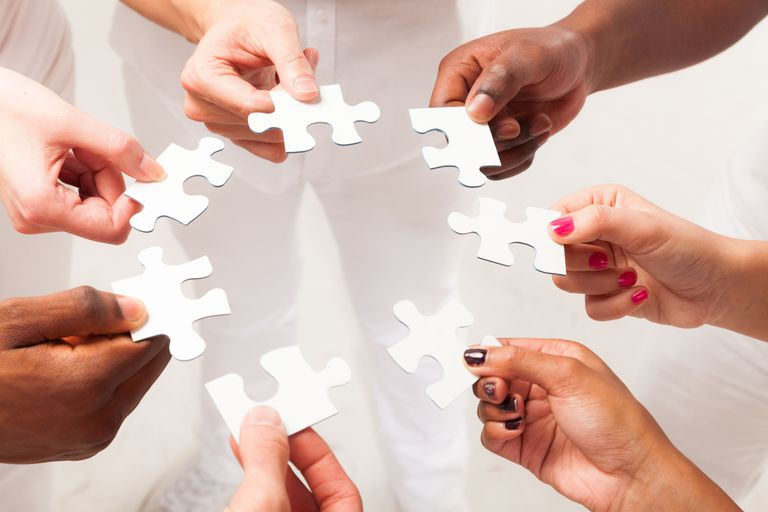 Hands of different skin color holding puzzle pieces of the same puzzle