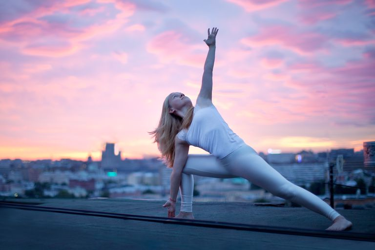 Woman doing yoga at sunrise