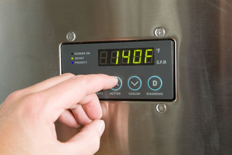Male Finger Turning Up Tankless Water Heater Temperature