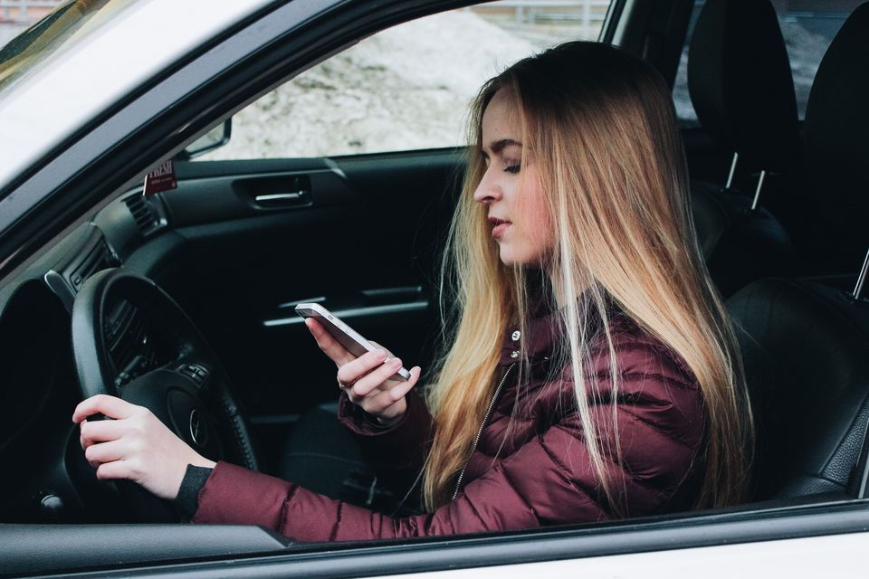 Young Woman Using Smart Phone In Car