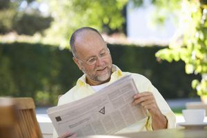 A senior man reading the paper in the garden