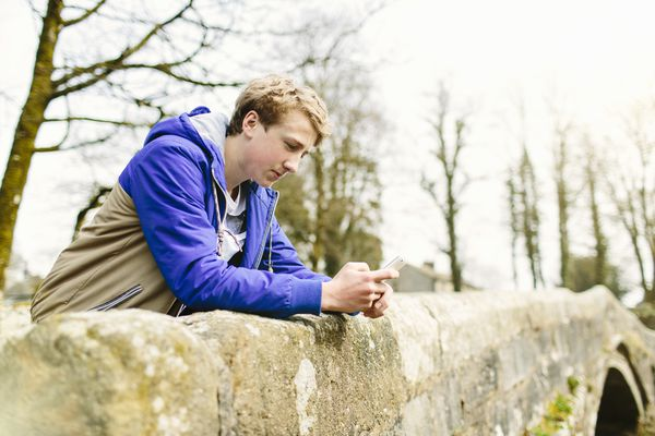 Unhappy teenage boy leaning over rural bridge.