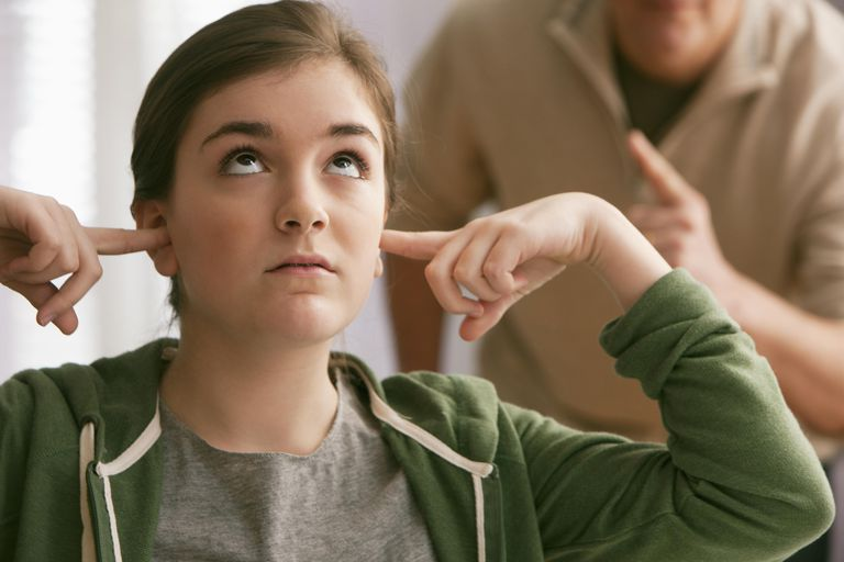 Daughter with fingers in ears as father scolds