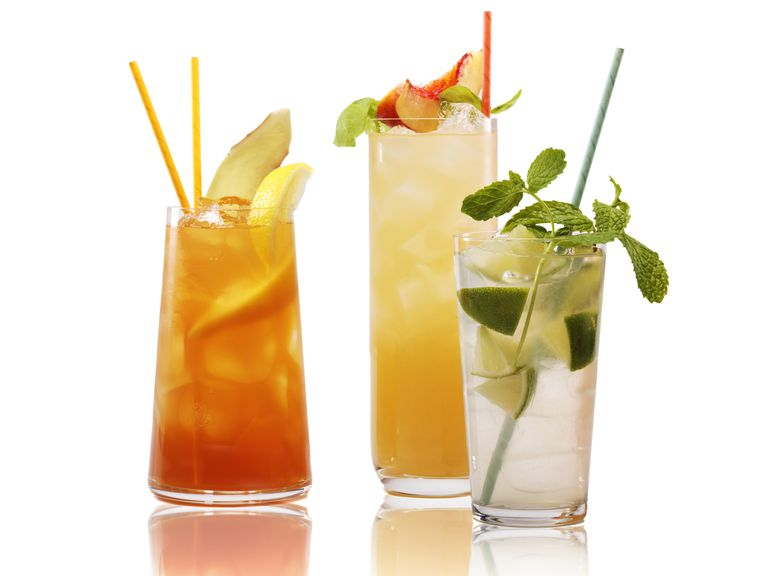 Cocktails in tall glasses with straws and fruit
