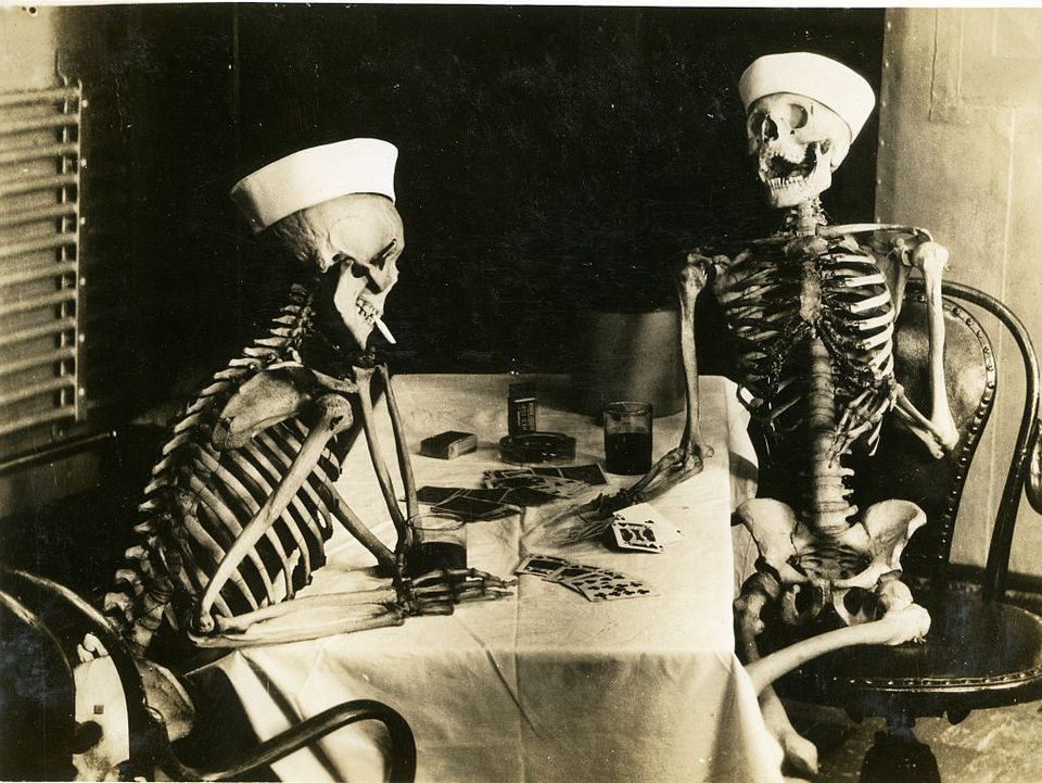 Skeletons wearing sailor hats playing cards.
