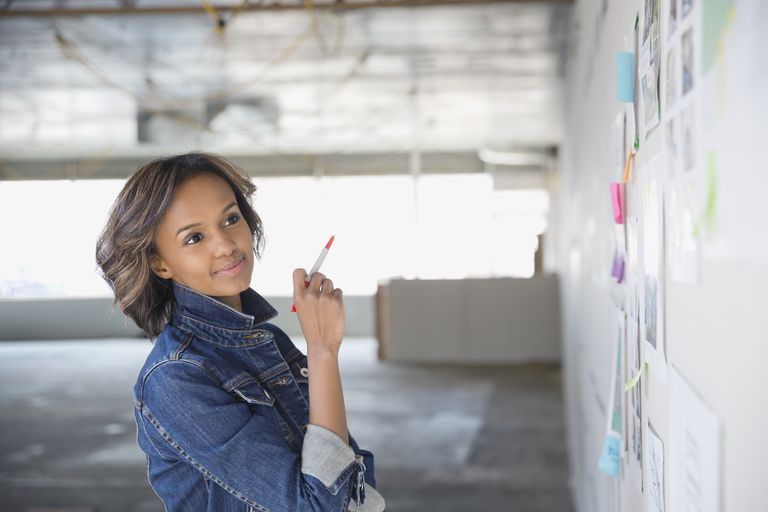 Confident businesswoman brainstorming at board in new office